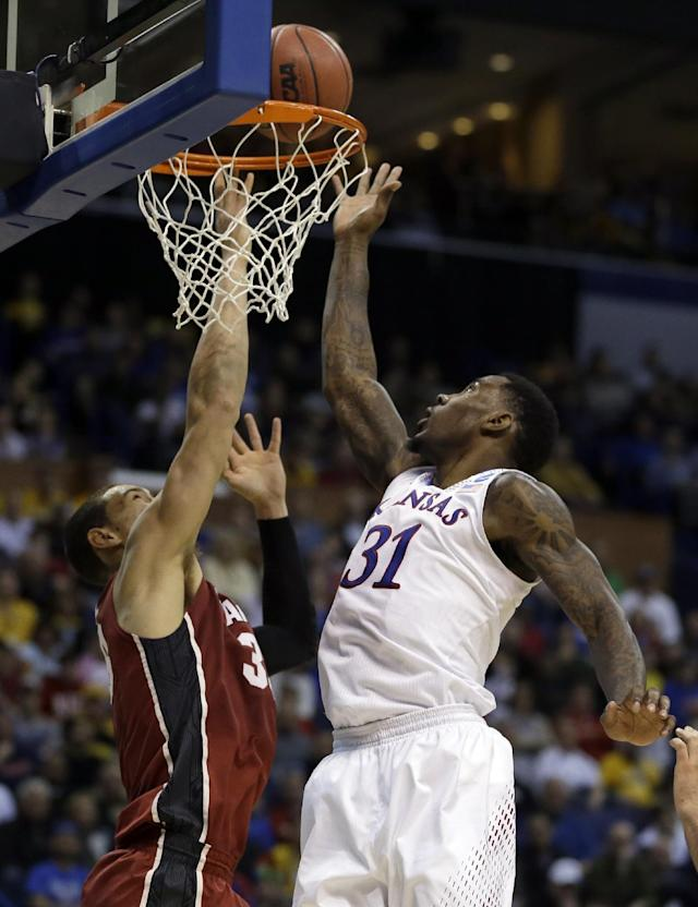 Kansas' Jamari Traylor, right, heads to the basket as Stanford's Dwight Powell defends during the first half of a third-round game of the NCAA college basketball tournament Sunday, March 23, 2014, in St. Louis. (AP Photo/Jeff Roberson)