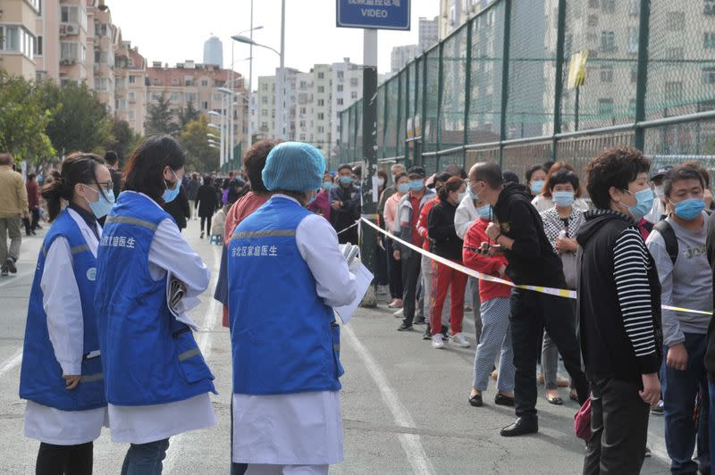FILE PHOTO: People wearing face masks line up for nucleic acid testing in Qingdao