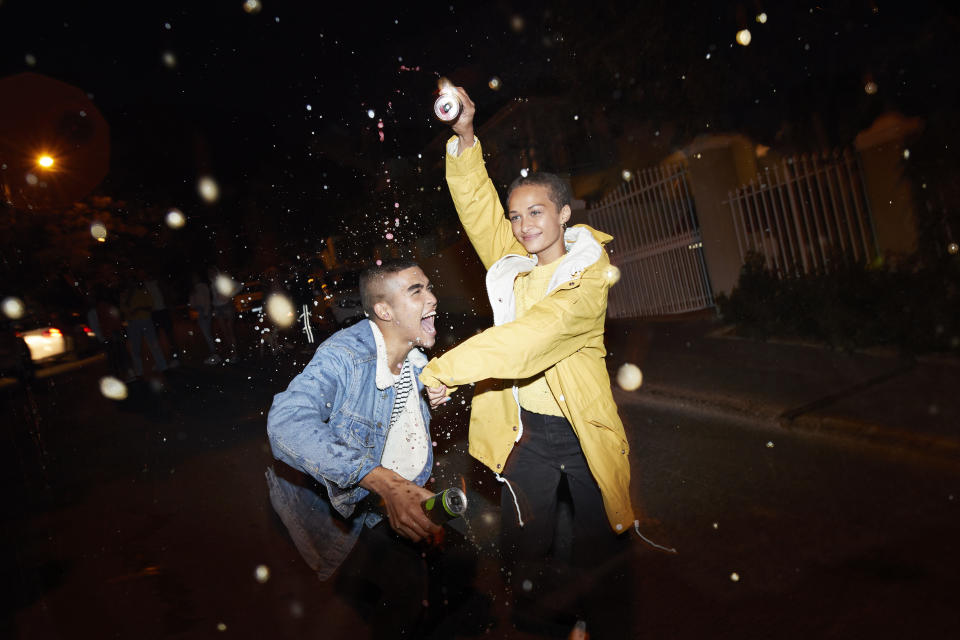 Happy young man and woman splashing drink and dancing on street at night