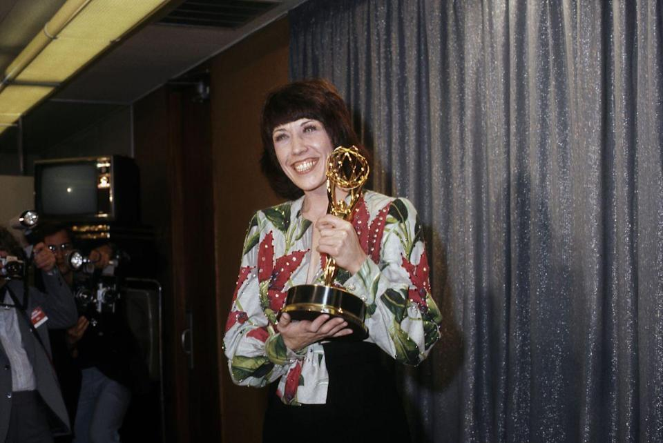 """<p>Tomlin slayed in a printed shirt when she picked up her Emmys (plural) for <em>Lily</em><span class=""""redactor-invisible-space""""> in 1974. </span></p>"""