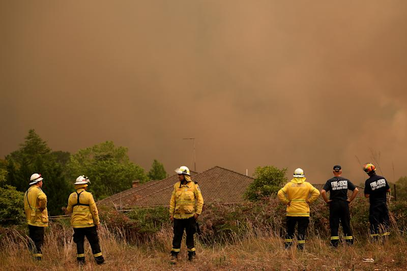 NSW Rural Fire Service and Fire and Rescue NSW firefighters watch on as the Grose Valley Fire approaches Kurrajong Heights, Saturday, December 21, 2019. Conditions are expected to worsen across much of NSW as temperatures tip 40C. (AAP Image/Dan Himbrechts)