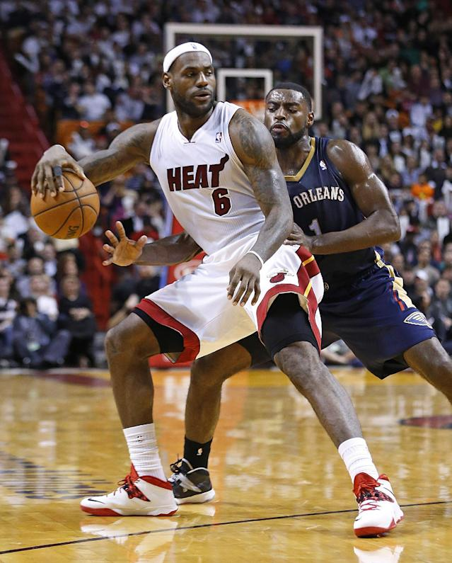 Miami Heat's LeBron James (6) dribbles the ball while being defended by New Orleans Pelicans' Tyreke Evans (1) during the second half of an NBA basketball game in Miami, Tuesday, Jan 7, 2014. The Heat defeated the Pelicans 107-88. (AP Photo/Joel Auerbach)