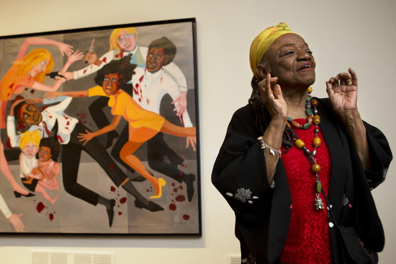"""Artist Faith Ringgold talks about her artwork in front of her painting, """"Die (1967)"""" during a press preview of her exhibition, """"American People, Black Light: Faith Ringgold's Paintings of the 1960s"""" at the National Museum of Women in the Arts in Washington, Wednesday, June 19, 2013. Ringgold explains her """"confrontational art"""" _ vivid paintings whose themes of race, gender, class and civil rights were so intense that for years, no one would buy them. """"I didn't want people to be able to look, and look away, because a lot of people do that with art,"""" Ringgold said. """"I want them to look and see. I want to grab their eyes and hold them, because this is America."""" (AP Photo/Jacquelyn Martin)"""