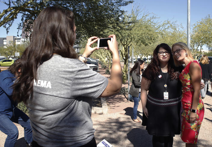U.S. Senate candidate Kyrsten Sinema, D-Ariz., takes selfies with supporters at the Barton Barr Central Library, Tuesday, Nov. 6, 2018 in Phoenix. Sinema and republican challenger Martha McSally are seeking the senate seat being vacated by Jeff Flake, R-Ariz., who is retiring in January.(AP Photo/Rick Scuteri)