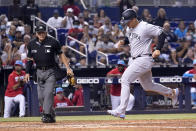 New York Yankees' Anthony Rizzo, right, scores on a wild pitch by Miami Marlins reliever Anthony Bender during the fifth inning of a baseball game, Saturday, July 31, 2021, in Miami. (AP Photo/Lynne Sladky)