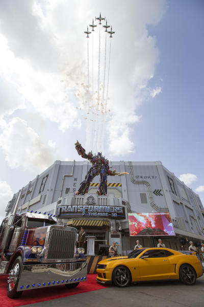 This image released by Universal Orlando shows a three-story-tall Optimus Prime figure at the entrance to the Transformers: The Ride-3D as a formation of private jets flies overhead at the grand opening of the attraction at Universal Orlando Resort, Thursday, June 20, 2013 in Orlando, Fla. (AP Photo/Universal Orlando Resort)