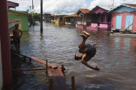 A boy jumps into a flooded street in Anama, Amazonas state, Brazil, Friday, May 14, 2021. Anama, home to residents who live on a tributary of the Solimoes River that flows toward the capital Manaus, is just one municipality of dozens in Amazonas state that has seen life upended by unusual rainfall. (AP Photo/Edmar Barros)