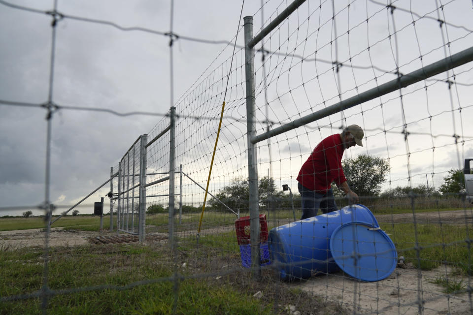 Migrant rights activist Eduardo Canales cleans out a blue water drop Saturday, May 15, 2021, in Falfurrias, Texas. Every week, Canales fills up blue water drums that are spread throughout a vast valley of Texas ranchlands and brush. They are there for migrants who venture into the rough terrain to avoid being caught and sent back to Mexico. (AP Photo/Gregory Bull)
