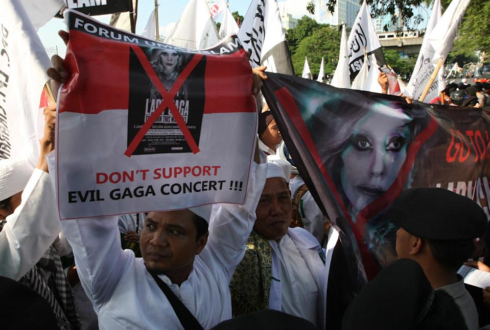 Muslim men hold up banners during a rally against U.S. pop singer Lady Gaga's concert that is scheduled to be held on June 3, outside the U.S. Embassy in Jakarta, Indonesia, Friday, May 25, 2012. Lady Gaga might have to cancel her sold-out show in Indonesia because police worry her sexy clothes and dance moves undermine Islamic values and will corrupt the country's youth. (AP Photo/Dita Alangkara)