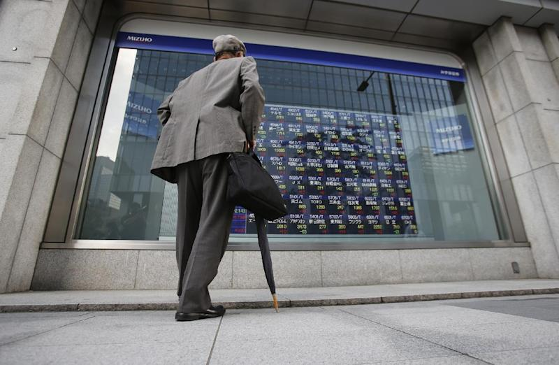 A man watches an electronic stock indicator of a securities firm in Tokyo, Tuesday, May 13, 2014. Asian stock markets rose after Wall Street indexes hit record highs, with Japan's Nikkei 225 leading gains as the yen weakened. The Nikkei ended up 275.92 points at 14,425.44 on Tuesday. (AP Photo/Shizuo Kambayashi)