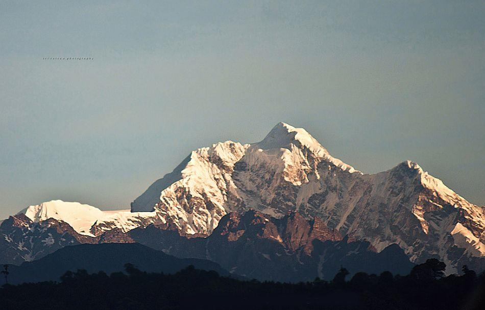Sikkim's presiding deity, the munificent Mount Kangchenjunga, reveals her sunlit snow crowns at dawn for a few minutes before hiding again beneath a quilt of monsoon clouds.