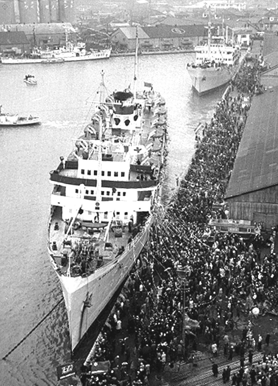 """In this Dec. 14, 1959, photo, the first two ships carrying 975 people depart for North Korea from the port of Niigata, Japan, after receiving a grand see-off. A Japanese court has summoned North Korea's leader to face demands for compensation by several ethnic Korean residents of Japan who say they suffered human rights abuses in North Korea after joining a resettlement program there that described the country as a """"paradise on Earth,"""" a lawyer and plaintiff said Tuesday. (Kyodo News via AP)"""