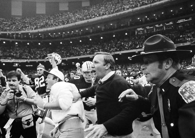 FILE - In this Jan. 3, 1984, file photo, Auburn head coach Pat Dye, center, rushes onto the field after his team beat Michigan 9-7 in the Sugar Bowl at the Superdome in New Orleans. Former Auburn coach Pat Dye, who took over a downtrodden football program in 1981 and turned it into a Southeastern Conference power, has died. He was 80. Lee County Coroner Bill Harris said Dye passed away Monday, June 1, 2020, at the Compassus Bethany House in Auburn, Ala.(AP Photo, File)