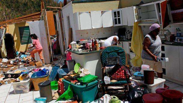 PHOTO: Family members collect belongings after hurricane force winds destroyed their house in Toa Baja, west of San Juan, Puerto Rico, on Sept. 24, 2017, following the passage of Hurricane Maria. (AFP via Getty Images, FILE)