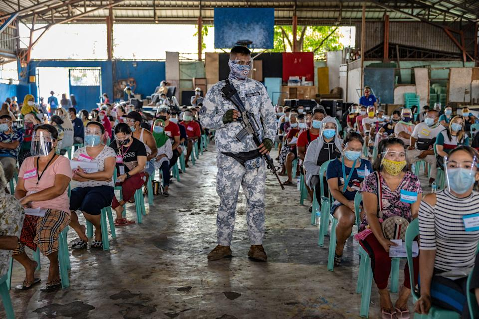 A soldier stands guard as residents out of work due to the coronavirus pandemic queue for ($20) cash aid on April 7,2021 in Manila, Philippines.