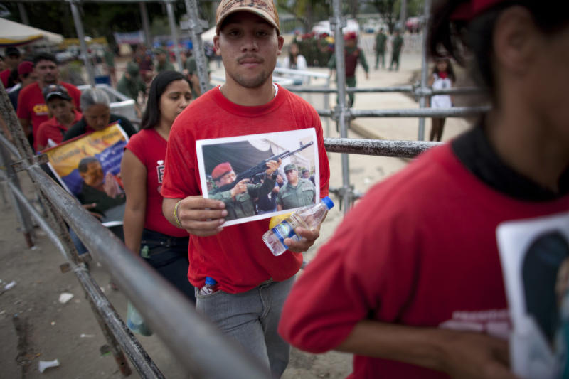 People enter the military academy to see the body of Venezuela's late President Hugo Chavez lying in state in Caracas, Venezuela, Sunday, March 10, 2013. Chavez died on March 5 after a nearly two-year bout with cancer. He was 58. (AP Photo/Ariana Cubillos)
