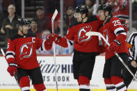 New Jersey Devils defensemen Andy Greene (6) and Mirco Mueller (25) congregate around left wing Miles Wood, center, after Wood scored during the first period of the team's NHL hockey game against the Montreal Canadiens, Tuesday, Feb. 4, 2020, in Newark, N.J. (AP Photo/Kathy Willens)