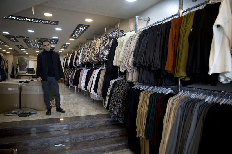 In this Wednesday, Feb. 12, 2020 photo, Palestinian shopkeeper Bilal Dwaik poses for a photo in his store, which sells clothes he imports from China, in the West Bank city Hebron. The local market has long been flooded by low-cost Chinese goods. Traders fear that if the outbreak and quarantine efforts continue they will have to switch to more expensive alternatives, passing higher prices onto consumers who may not be able to bear them. (AP Photo/Majdi Mohammed)