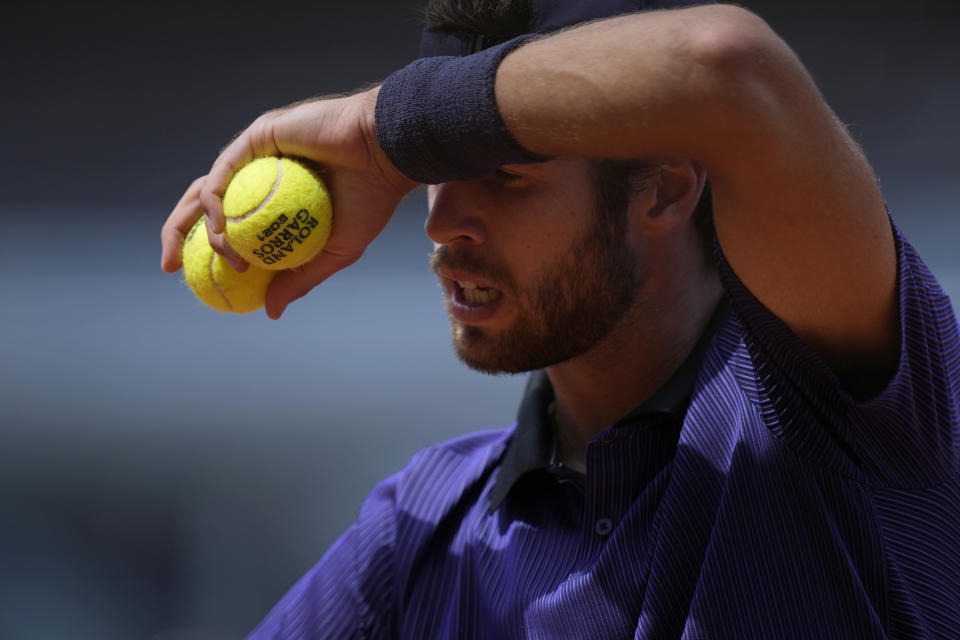 Russia's Karen Khachanov wipes his face as he prepares to serve to Japan's Kei Nishikori during their second round match on day four of the French Open tennis tournament at Roland Garros in Paris, France, Wednesday, June 2, 2021. (AP Photo/Thibault Camus)