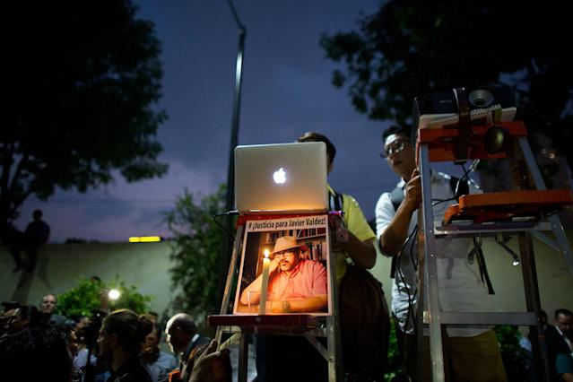 <p>A pair of young men project a video and slideshow from atop ladders, one decorated with a picture of murdered journalist Javier Valdez, during a protest in front of the Interior Ministry in Mexico City, Tuesday, May 16, 2017. (AP Photo/Rebecca Blackwell) </p>