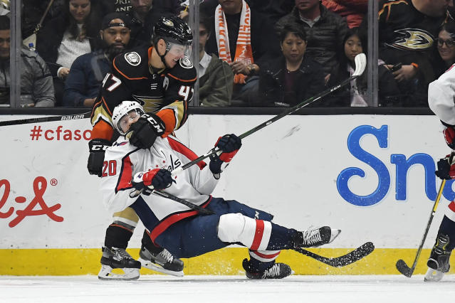 Anaheim Ducks defenseman Hampus Lindholm, left, takes down Washington Capitals center Lars Eller during the second period of an NHL hockey game Friday, Dec. 6, 2019, in Anaheim, Calif. (AP Photo/Mark J. Terrill)