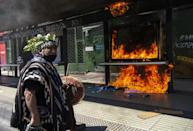 A Mapuche indigenous man plays a tambourine as he marches past an advertisement set on fire by demonstrators who clashed with riot police during a protest in Santiago