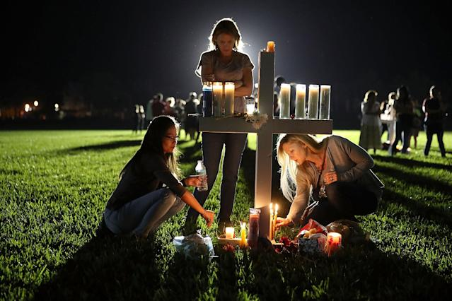 <p>Maria Reyes, Stacy Buehler and Tiffany Goldberg light candles around a cross as they attend a candlelight memorial service for the victims of the shooting at Marjory Stoneman Douglas High School that killed 17 people on Feb. 15, 2018 in Parkland, Fla. (Photo: Joe Raedle/Getty Images) </p>