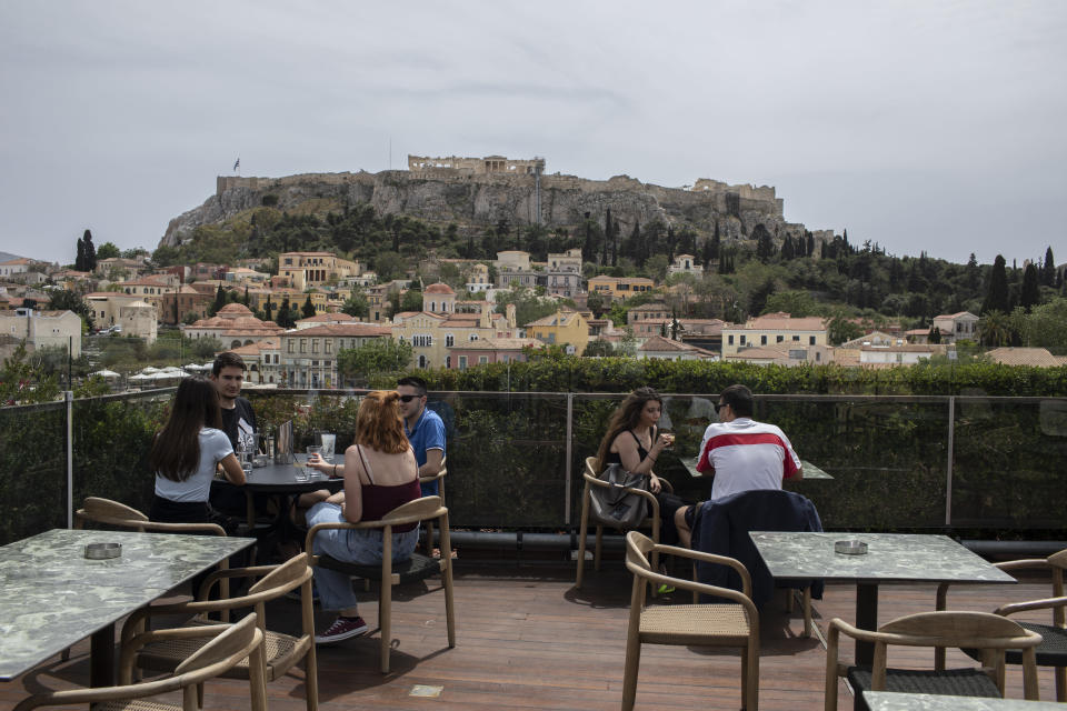 People sit in on a cafe terrace, in the Monastiraki district of Athens, with the ancient Acropolis hill in the background, Monday, May 3, 2021. Cafes and restaurants have reopened in Greece for sit-down service for the first time in nearly six months, as the country began easing coronavirus-related restrictions with a view to opening to the vital tourism industry in the summer. (AP Photo/Petros Giannakouris)
