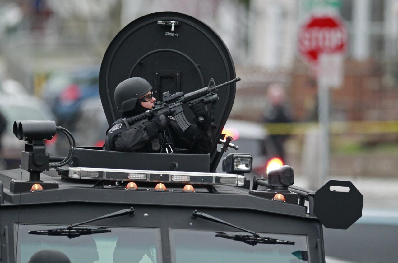 Police in tactical gear arrive on an armored police vehicle as they surround an apartment building while looking for a suspect in the Boston Marathon bombings in Watertown, Mass., Friday, April 19, 2013. The bombs that blew up seconds apart near the finish line of the Boston Marathon left the streets spattered with blood and glass, and gaping questions of who chose to attack and why. (AP Photo/Charles Krupa)