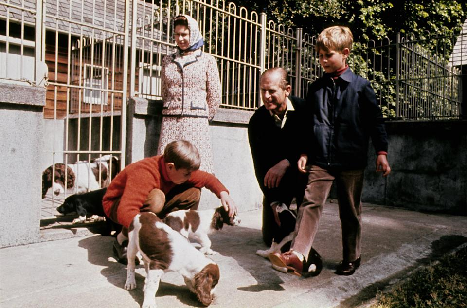 The queen, Duke of Edinburgh, Prince Andrew (left, in red) and Prince Edward visit the kennels at Balmoral in 1972.