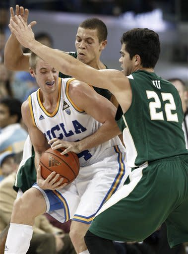 UCLA forward Travis Wear, left, is double teamed by Cal Poly's Drake U'u (22) and Chris Eversley during the first half of an NCAA college basketball game in Los Angeles, Sunday, Nov. 25, 2012. (AP Photo/Jason Redmond)