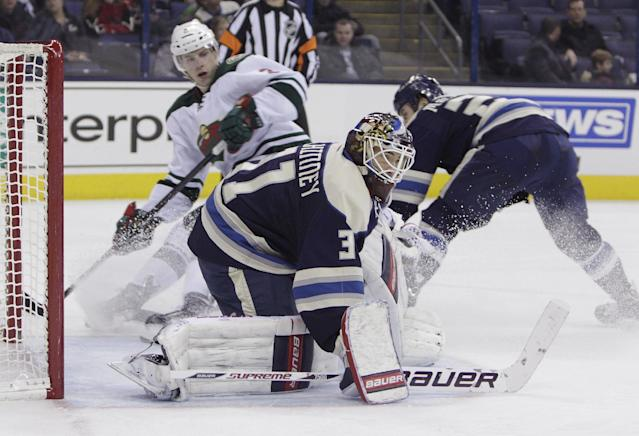 Columbus Blue Jackets' Curtis McElhinney, front, makes a save as teammate Derek MacKenzie, right, and Minnesota Wild's Charlie Coyle look for the puck during the third period of an NHL hockey game on Friday, Dec. 6, 2013, in Columbus, Ohio. The Blue Jackets won 4-0. (AP Photo/Jay LaPrete)
