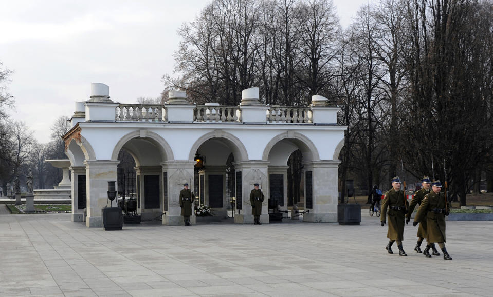 FILE - In this Dec. 9, 2014 file photo, soldiers walk after changing the guard at the Tomb of the Unknown Soldier, the only remaining part of the Saski Palace, in Warsaw, Poland. Poland is reviving plans to reconstruct a historic Warsaw palace where the German Enigma machine codes were first cracked in 1932 and which Nazi German occupying forces blew up in 1944, it was announced Wednesday, July 7, 2021. The palace once housed a cipher office where the German Enigma encoding machine was first cracked. Only a colonnade that contains the Tomb of the Unknown Soldier still survives. Plans to have the palace rebuilt have been made ever since the war's end. (AP Photo/Alik Keplicz, file)
