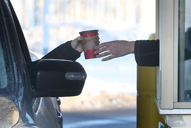 A tea is passed to a customer at the drive thru in Toronto. January 10, 2018. (Steve Russell/Toronto Star via Getty Images)