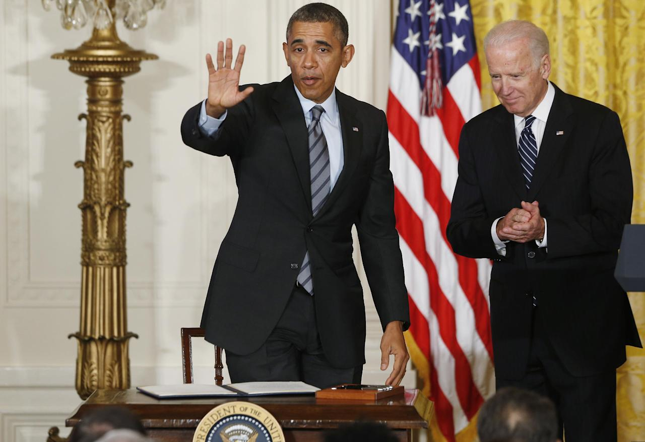 President Barack Obama waves to the audience after he signed a presidential memo directing the federal government not to discriminate against those long-term unemployed workers in its own hiring practices during an event in the East Room at the White House in Washington, Friday, Jan. 31, 2014. Vice President Joe Biden is at right. (AP Photo/Charles Dharapak)