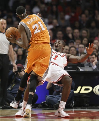 Chicago Bullsguard Ronnie Brewer (11) takes the charge from Phoenix Suns forward Hakim Warrick (21) during the first half of an NBA basketball game Tuesday, Jan. 17, 2012, in Chicago. (AP Photo/Charles Rex Arbogast)