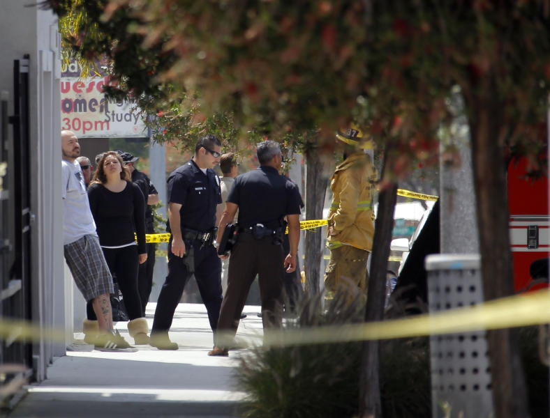 Los Angeles Police officers gather at the site where police arrested a man after discovering explosive material in his car and potential explosive devices in his apartment Wednesday May 15, 2013 in Los Angeles. Four buildings have been evacuated and several blocks have been sealed off. Police are withholding the man's name until the investigation has concluded.(AP Photo/Nick Ut)