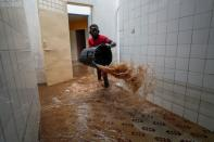 Volunteer removes water from a flooded health center after heavy rains in Guediawaye on the outskirts of Dakar