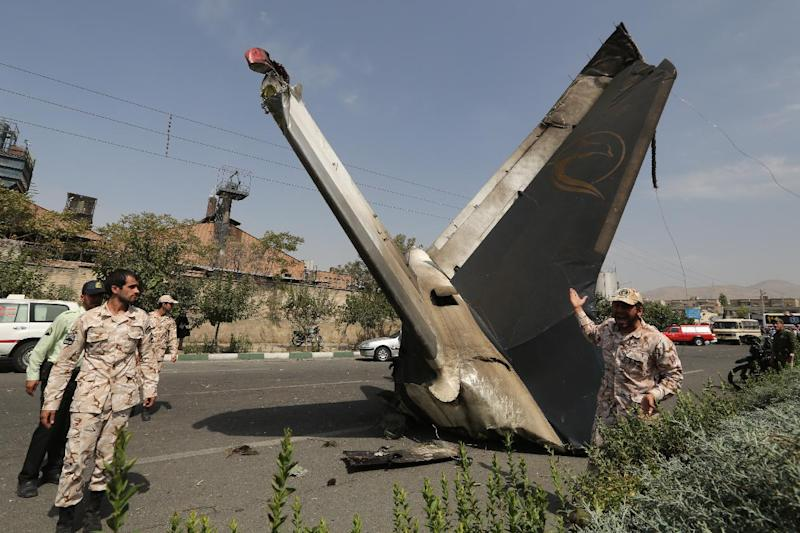 A member of the Iranian Revolutionary Guards stands next to the remains of a plane that crashed near Tehran's Mehrabad airport, on August 10, 2014