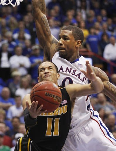 Missouri guard Michael Dixon (11) tries to shoot while covered by Kansas forward Thomas Robinson (0) during the second half of an NCAA college basketball game in Lawrence, Kan., Saturday, Feb. 25, 2012. Kansas defeated Missouri 87-86 in overtime. (AP Photo/Orlin Wagner)