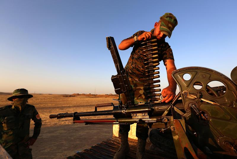 An Iraqi Kurdish Peshmerga fighter loads a gun on the front line in Khazer, near the Kurdish checkpoint of Aski kalak, on August 14, 2014