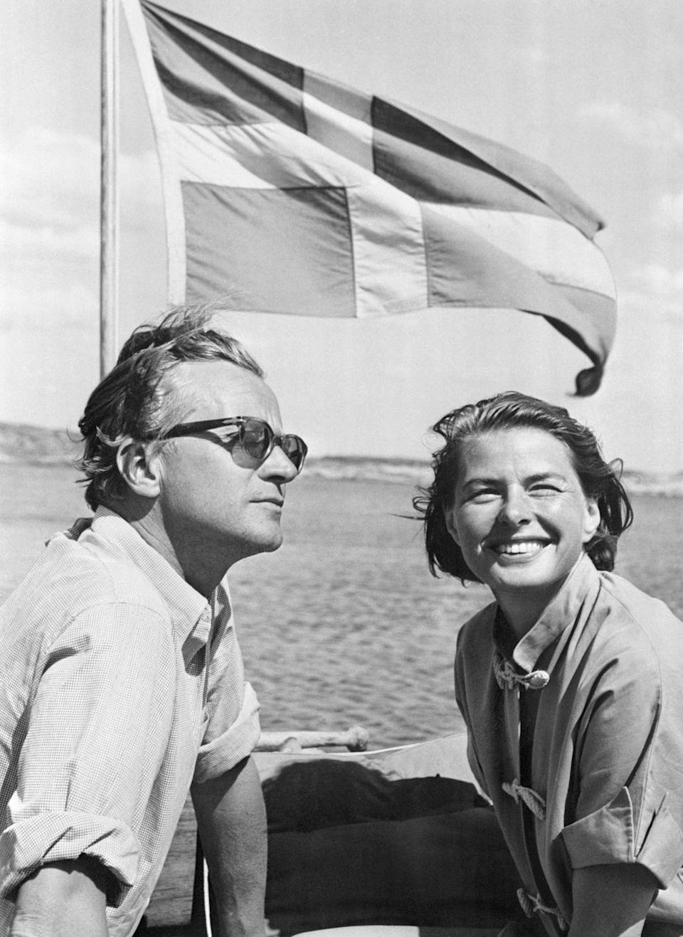 <p>Ingrid Bergman and her husband, Lars Schmidt, sit in front of the Swedish flag flying off the back of their sailboat, the Mayflower. The Swedish film star sports wind-blown hair and smiles for the camera in a cotton button-down. </p>