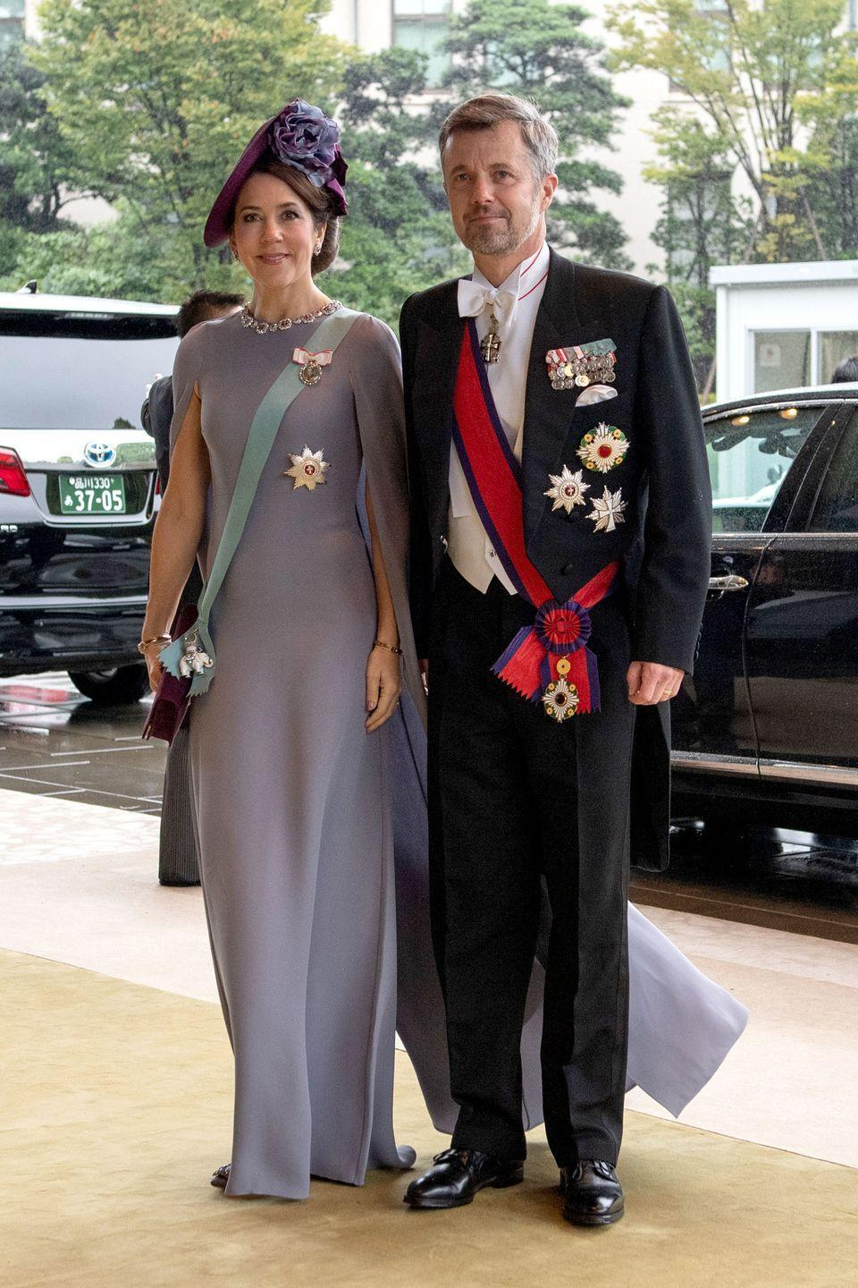 """<p>Apparently, cape dresses were a trend at Emperor Naruhito's enthronement ceremony. <a href=""""https://www.townandcountrymag.com/society/tradition/g30447253/princess-mary-fashion-style/"""" rel=""""nofollow noopener"""" target=""""_blank"""" data-ylk=""""slk:Crown Princess Mary"""" class=""""link rapid-noclick-resp"""">Crown Princess Mary</a> sported her cape gown in a lilac shade. Mary was not afraid to accessorize, as she paired the look with a bold necklace and a striking purple, floral hat. <br></p>"""
