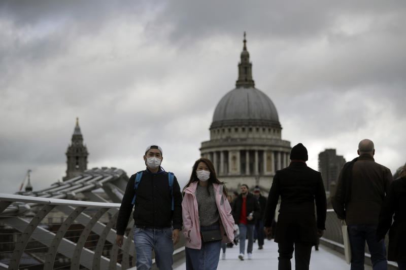 "People wearing face masks walk across the Millennium footbridge backdropped by the dome of St Paul's Cathedral in London, Tuesday, March 10, 2020. Starkly illustrating the global east-to-west spread of the new coronavirus, Italy began an extraordinary, sweeping nationwide travel ban on Tuesday while in China, the diminishing threat prompted the president to visit the epicenter and declare: """"We will certainly defeat this epidemic."" (AP Photo/Matt Dunham)"