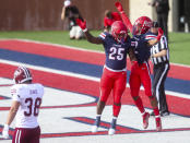 Liberty wide receiver Kevin Shaa (2) celebrates his touchdown with teammate running back Peytton Pickett (25) as Massachusetts safety Tanner Davis (38) walks away during the first half of a NCAA college football game on Friday, Nov. 27, 2020, at Williams Stadium in Lynchburg, Va. (AP Photo/Shaban Athuman)