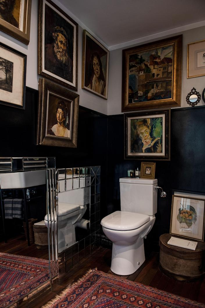 In the guest bathroom on the ground floor, the walls are covered with Broudo's father's beloved oil paintings.