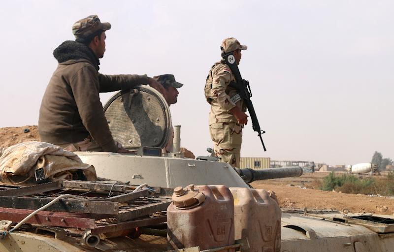 Iraqi forces stand guard near the Al-Qaim border crossing with Syria on November 8, 2017