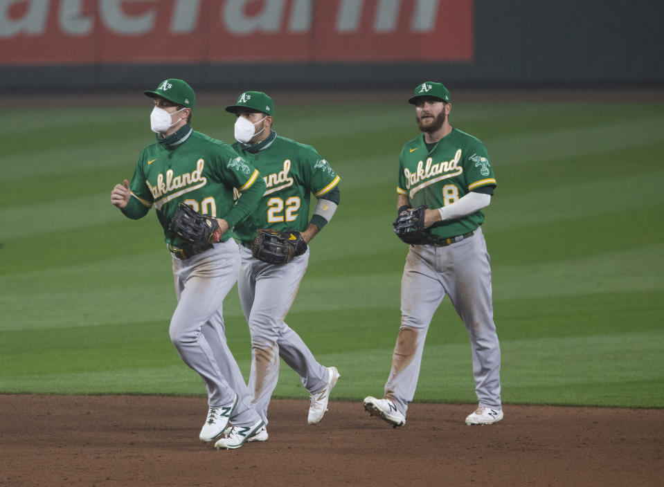 The Oakland A's outfield jogs in during a 2020 game, with Mark Canha and Ramon Laureano wearing masks. The 2021 season is likely to be played under the same sort of protocols. (Photo by Lindsey Wasson/Getty Images)