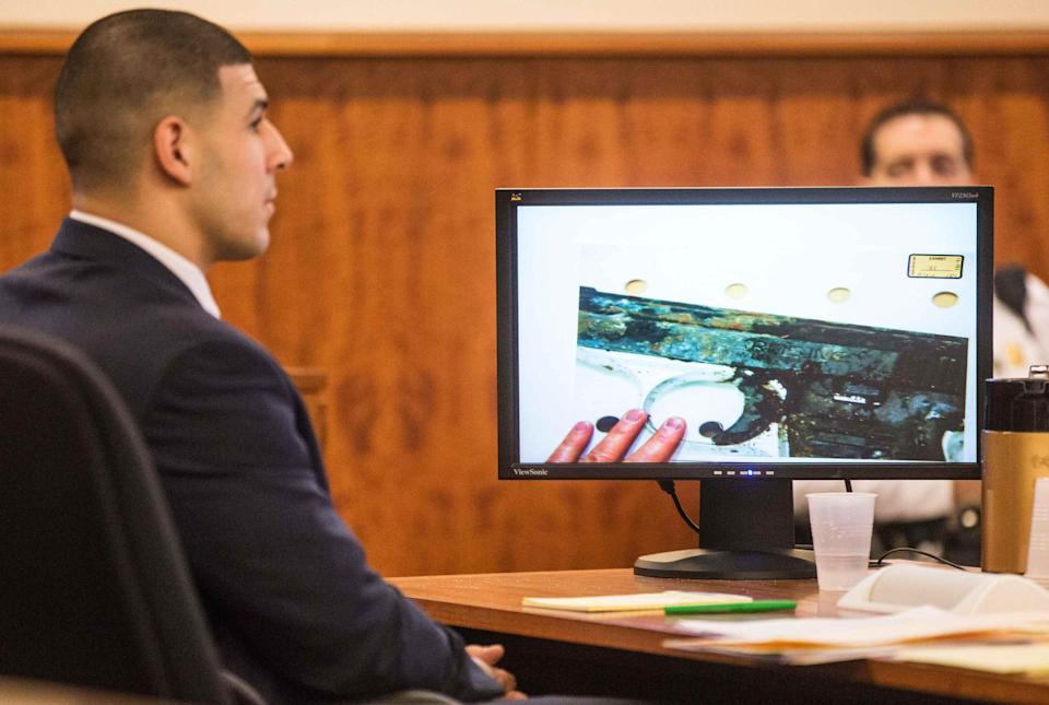 Former New England Patriots player Aaron Hernandez listens as a photo of a small handgun found in a wooded area near the crime scene was displayed during his murder trial at the Bristol County Superior Court in Fall River, Massachusetts February 13, 2015. REUTERS/Aram Boghosian/Pool (UNITED STATES - Tags: CRIME LAW SPORT FOOTBALL)