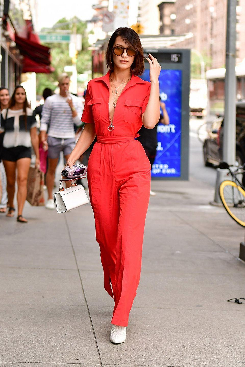 <p>In a red jumpsuit with white leather ankle boots and a leather clutch while out in New York City.</p>
